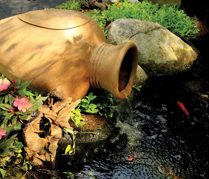 A beautiful vase water feature in the garden with a fish pond